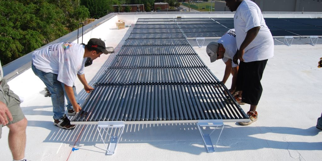 Construction team place down thermal solar coils