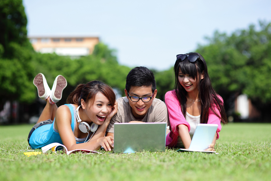 Three students sitting in a grass field, smiling at a shared laptop screen