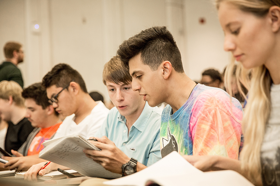 Students engaged in class compare notes during lecture