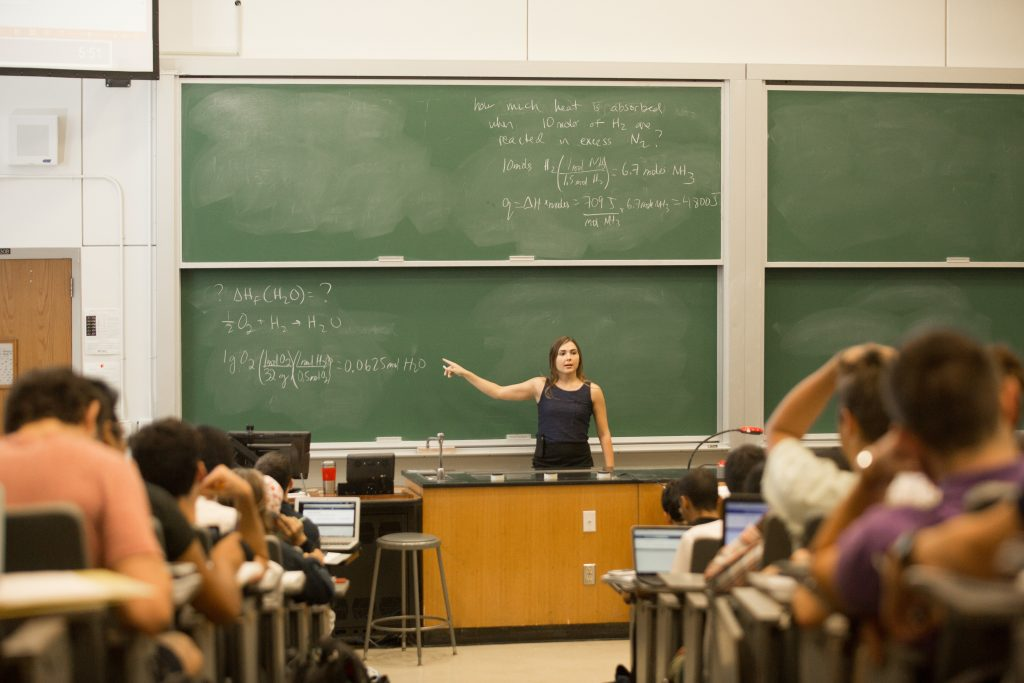 Professor points at chalk board in full college lecture hall