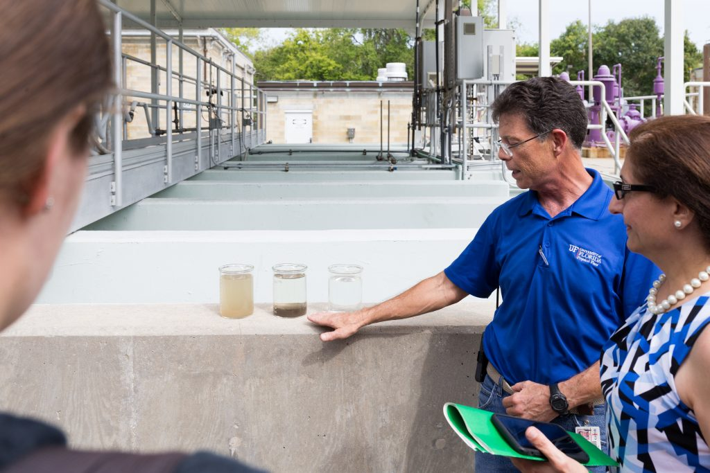 Guite at UF Waste Water Treatment Plant shows students water at three different stages of water filtration, from most least filtered to most filtered.
