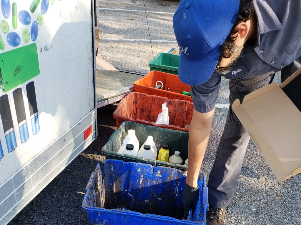 Man places material into blue recycling bin. Green and orange bins are visible behind him.