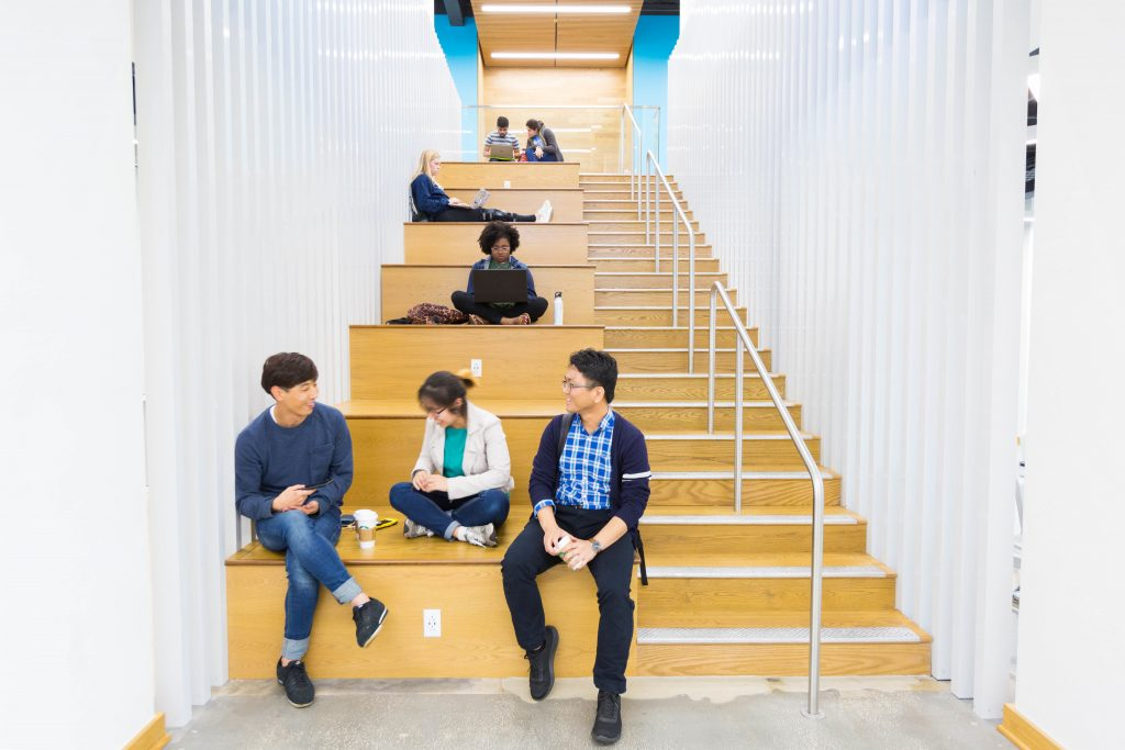 Students sit and talk on Newell Hall stairs