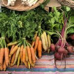 Beets and carrots on display in a farmers market