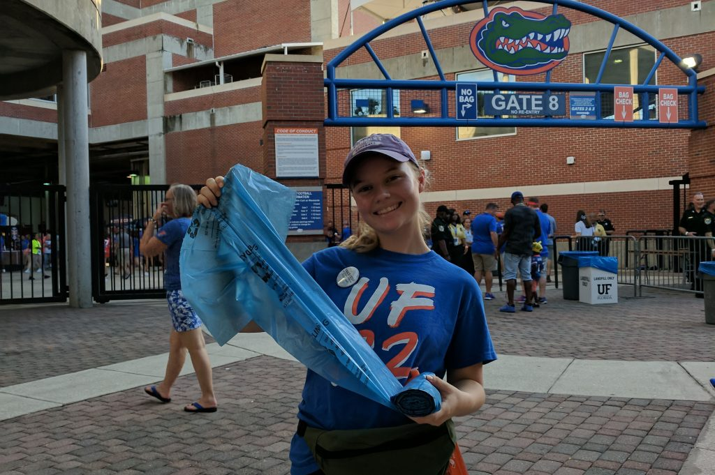 UF Tailgator volunteer smiling while holding a recycling bag in front of Ben Hill Griffin Statium