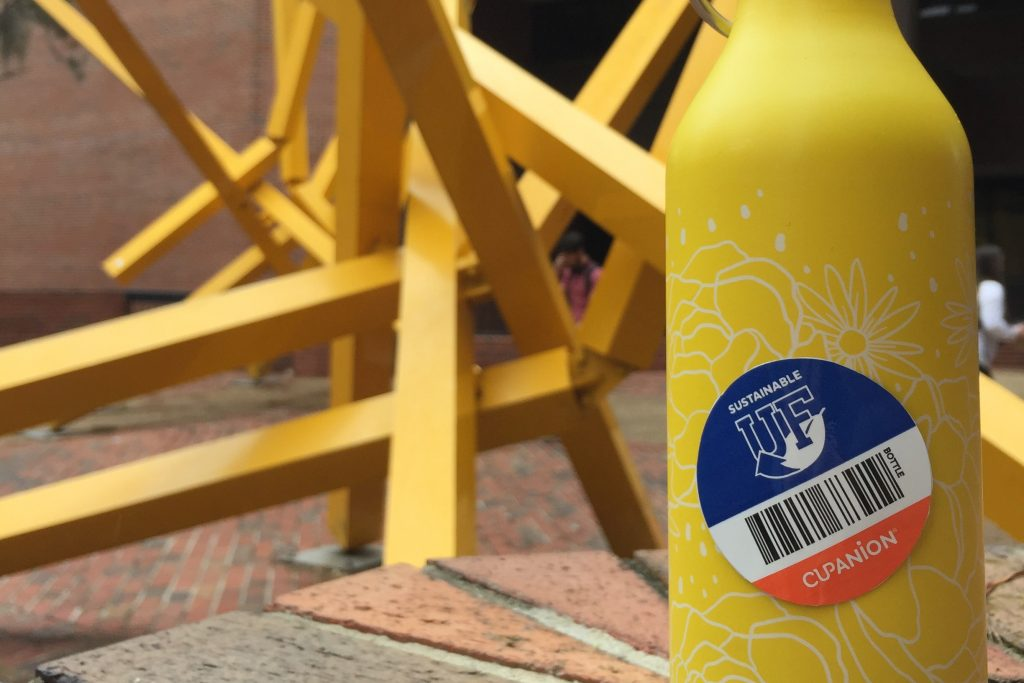 A yellow water bottle with a Cupanion sticker placed in front of the yellow Marston french fry state