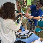 Two students are working together to place new tires on a bicycle during the Sustainable Transportation Fair