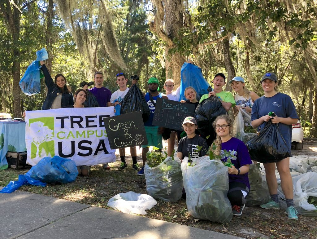 Student participants pose for their Tree Campus USA invasive species cleanup