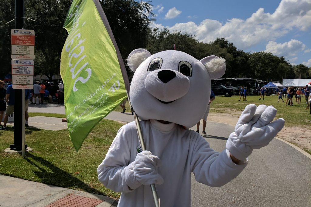 Susty, the Sustainable UF Polar Bear Mascot, waves at the camera while carrying a Sustainable UF Flag
