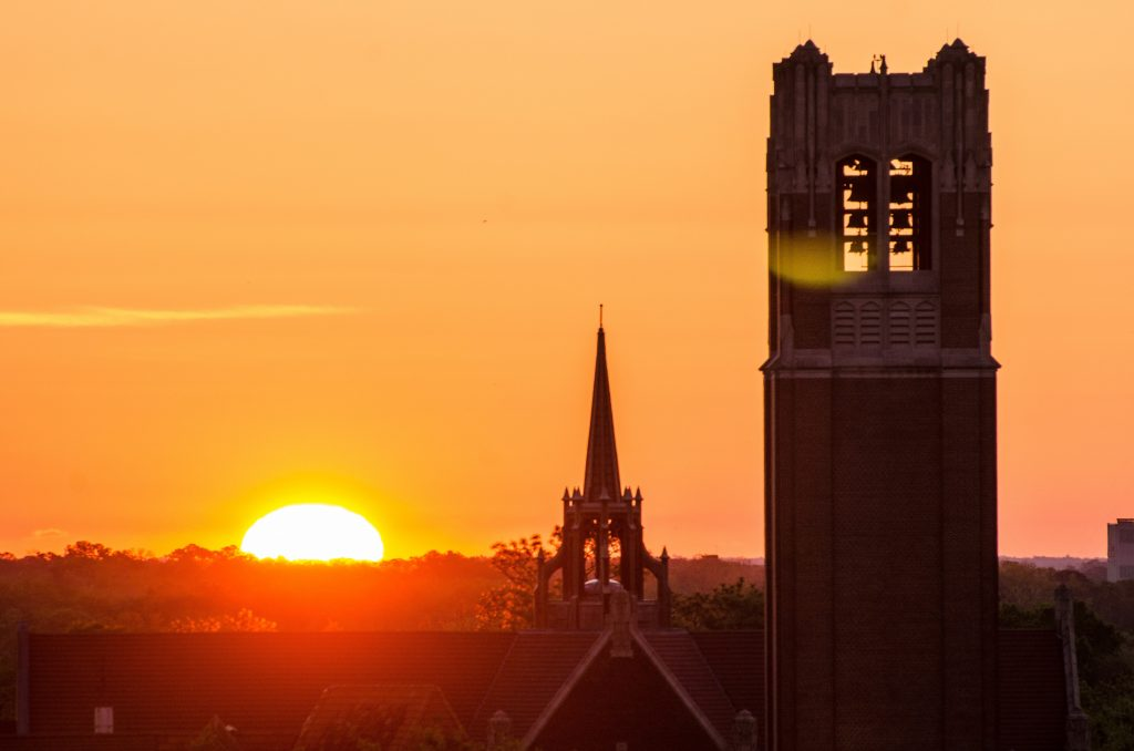 The top of Century Tower and University Auditorium as the sun sets on the horizon