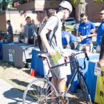 Student with bicycle stops at Sustainable Transportation Fair tables