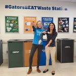 Two student volunteers doing the Gator Chomp infront of the GatorsBeatWaste Station