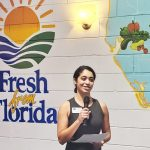 """Gator Dining Services sustainability manager Kayla Caselli-Bido speaking in front of the """"Fresh from Florida"""" mural"""