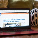Laptop showing an online cycling course on a couch next to a helmet