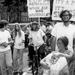 Students march with environmental protest signs, girl in shopping cart is pushed by a boy, next to a bicycle.